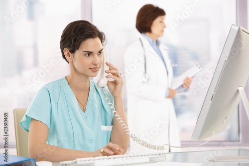 Medical assistant on phone, using computer - 23610465