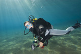 Young female scuba diver in clear blue water.