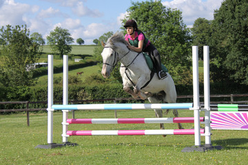 Teenage girl jumping pony