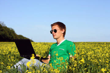 Happy student with laptop sitting at the grass