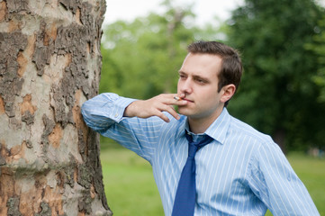 Young businessman smoking in a park