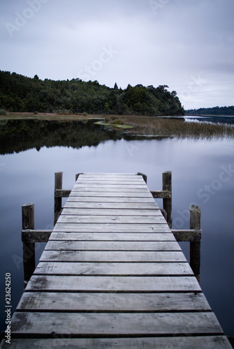 Obraz na Szkle Wooden Jetty stretches out on glassy Lake Brunner in New Zealand