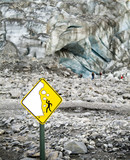 Terminal face of a glacier with a warning sign and people