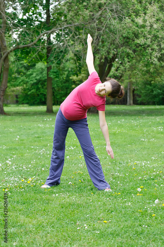Beautiful pregnant woman exercising in the park