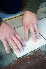 Detail of mason tiler hands laying a tile on the floor