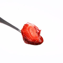 Piece of a strawberries covered with jelly on a spoon