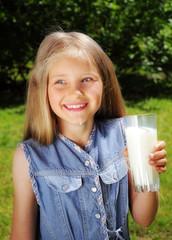 Little happy girl drinking milk