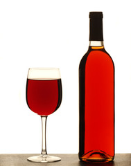 Wine glass and bottle of red wine against white background