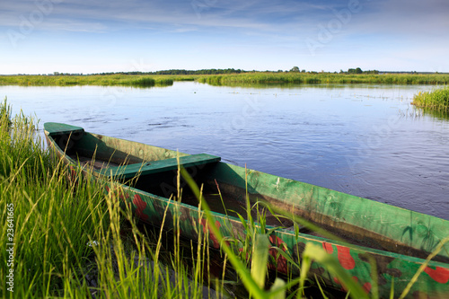 Landscape with wild river and boat in summer