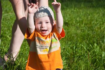 beautiful little boy looks in green summer meadow