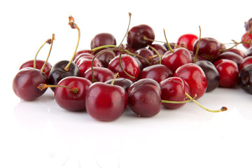 fresh cherries in closeup over white background
