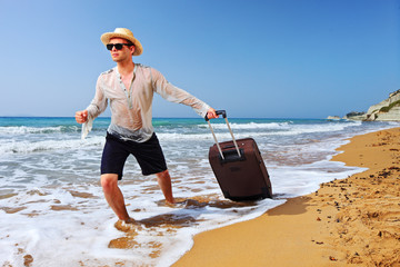 A tourist carrying a suitcase at the beach at Corfu island