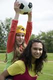Mädchen mit Kind Huckepack mit Fussball in der Hand poster