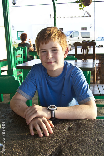 young boy is sitting on a table in a restaurant