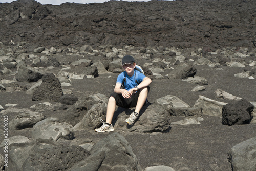 boy sitting on a stone on an  vulcanic beach