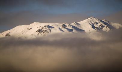 Mountain rises through cloud