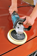 Worker waxing orange car by polishing machine