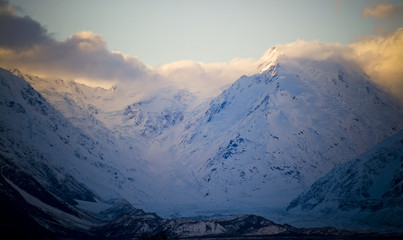 Sunset clouds sweep over icy peaks and a huge, glacial valley