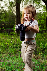 Amusing little girl takes pictures a professional camera