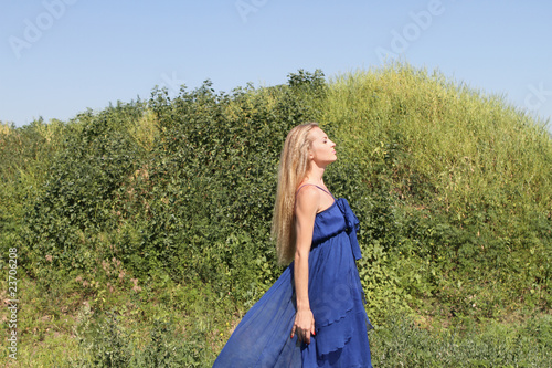 Blond girl in the blue dress on the green background