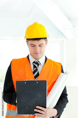 Serious male architect holding blueprints