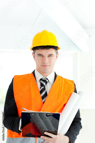 Confident male architect holding blueprints