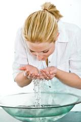 junge Frau reinigt ihr Gesicht mit Wasser
