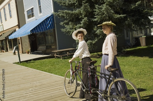 Two Women With A Vintage Bicycle Built For Two