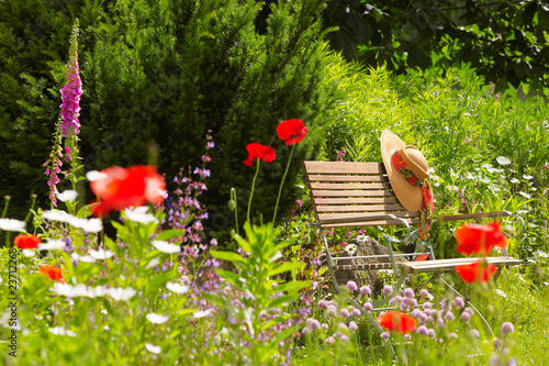 Leinwandbild Motiv garden bench with straw hat within summer flowers 01