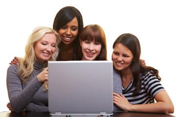 Vier Frauen schauen auf einen Laptop