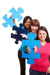 Drei Frauen zeigen Puzzleteile