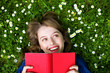 Woman lying on grass, reading book - 23735298
