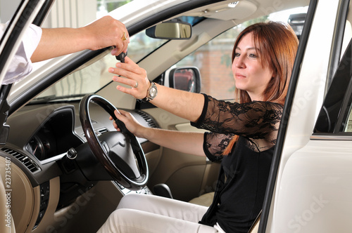 Red head woman buying a a new car.