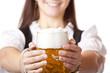 Nahaufnahme eines Oktoberfest Bierkrugs mit Frau im Hintergrund