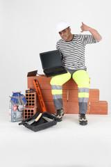 Ouvrier assis devant un ordinateur portable