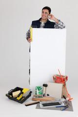 Carreleur téléphonant devant un panneau blanc
