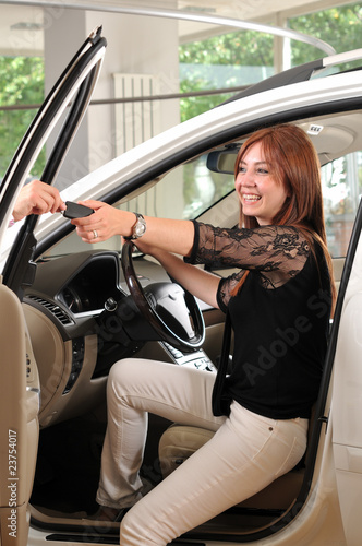 Car dealer giving keys of new car to happy red head customer.