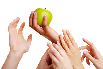 Viele Hände greifen nach Apfel