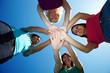Vier Frauen stapeln ihre Hände