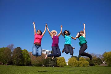 Vier Frauen springen im Park
