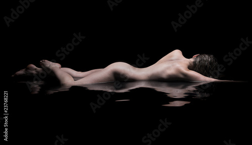 Fotobehang Akt Nude woman lies in water, low key