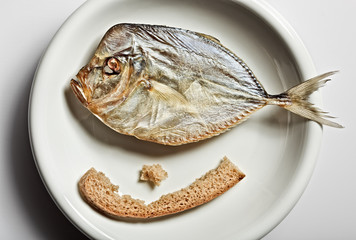 Salted moonfish with crust of bread on white plate