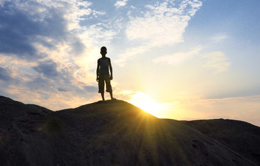 young man in sand desert in sundown silhouette