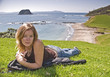 Blonde woman sitting on grass in New Zealand.