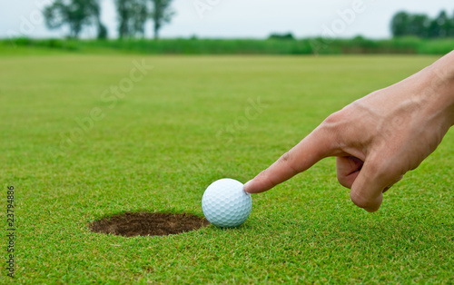 Man's hand pushing golf ball into the hole