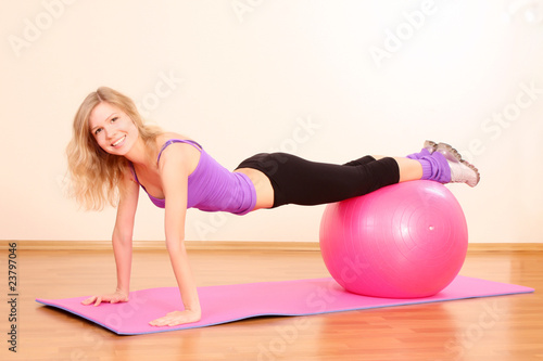 Young beautiful fitness girl with pink ball exercising in the gy