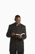 A Man Wearing A Clerical Collar And Reading From His Bible