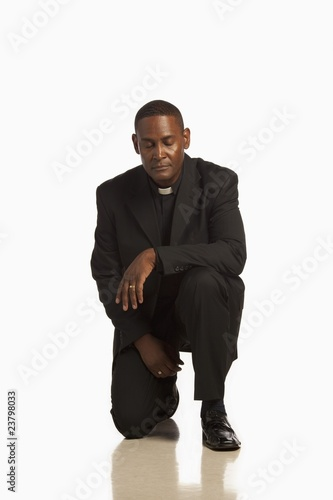 A Man Wearing A Clerical Collar Kneeling In Prayer