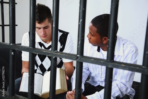 A Young Man Reads The Bible To Another Young Man In Jail