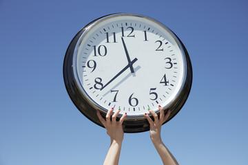 Hands lifting big clock outdoors